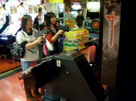 """A couple of girls trying out """"House of the Dead 4""""."""