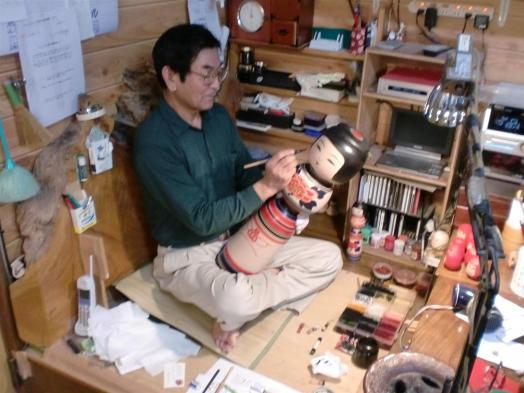 A kokeshi artist hard at work on a larger variety.
